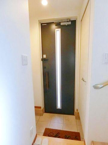 シューズボックスの完備された玄関です。家族を見送り、迎える空間だから日が差し込む明るい雰囲気の玄関扉を使っています。