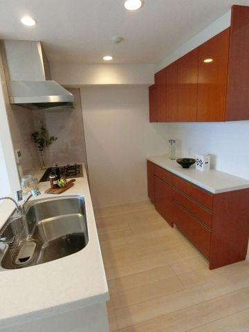 リビング全体を見渡せる対面式、オープン型のシステムキッチン。キッチンと配色を合わせたカップボード、大型冷蔵庫も収納可能なスペース。食洗機等の便利な設備も完備しております。