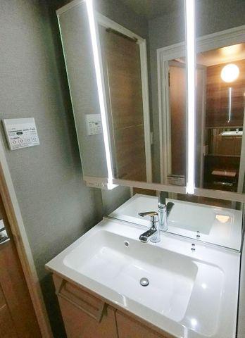 木目が暖かさを感じさせてくれる洗面台。3面鏡も付いて機能的な洗面台です。