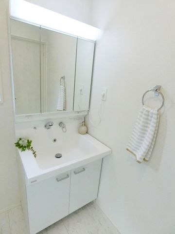 白を基調とした清潔感のある洗面台。3面鏡も付いて機能的な洗面台です。(1号棟)