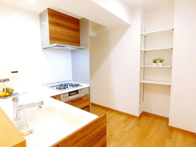 リビング全体を見渡せる対面式、オープン型のシステムキッチン。キッチンと配色を合わせたカップボード、大型冷蔵庫も収納可能なスペース。