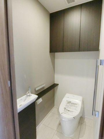 新品のトイレです。手洗い場、吊戸棚が付いております。スタイリッシュなタンクレスデザイン。