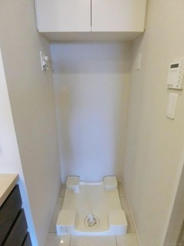 洗面所には、洗濯機置き場がございます。上部収納があり、すっきりとした印象です。