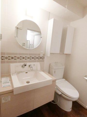 まるでホテルのような、統一性が取れた洗面スペース。洗面台下とトイレ上部に収納がございますので、いつでもすっきりとした空間です。