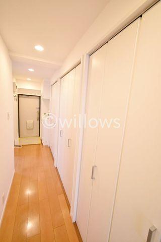 木目が暖かさを感じさせてくれる廊下部分。壁一面に収納が有り、お掃除用具や趣味用品など、ご自由に収納可能でございます。