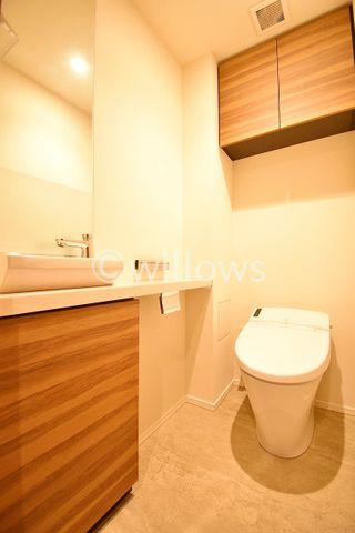 タンクレス型のトイレはお掃除も簡単。空間を広く使う工夫が随所に見受けられます。 より快適にご利用いただくために、人気のウォシュレットタイプを採用。上部の吊戸棚はトイレ用品の収納が可能です。
