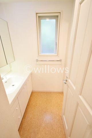 温かみのある色合いの洗面スペース。3面鏡も付いて機能的な洗面台です。窓が有り開放感がございますね。