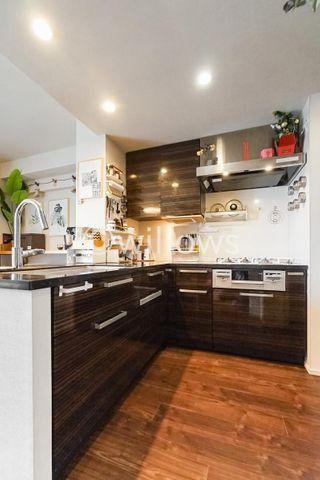 リビング全体を見渡せる対面式、オープン型のシステムキッチン。キッチンと配色を合わせた吊戸棚、大型冷蔵庫も収納可能なスペース。L字型のキッチンはスペースも広く便利です。