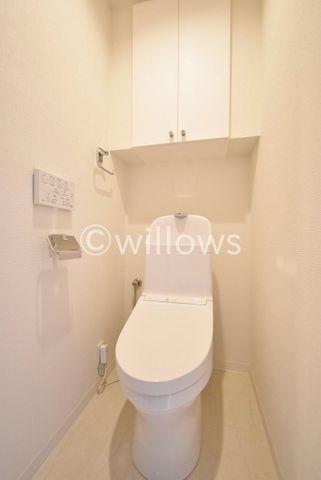 白を基調とした清潔感の高いお手洗い。上部の吊戸棚はトイレ用品の収納が可能。とても快適にご利用いただけます。