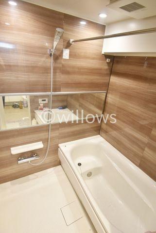木目調のアクセントのあるバスルームでございます。1416サイズのゆったり空間です。浴室乾燥機もついておりますので、天気に関係なく、洗濯物が乾きますね。