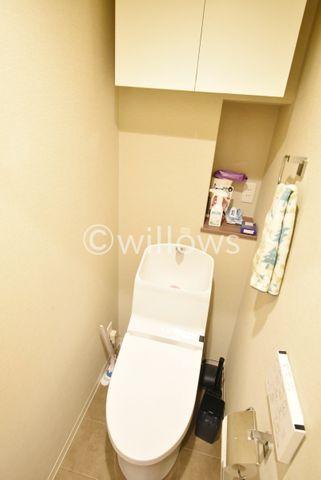 上部に収納とミニカウンターがある温水洗浄便座付きのトイレでございます。フロアタイルもアクセントがあり、インテリアがしっかりと映えますね。