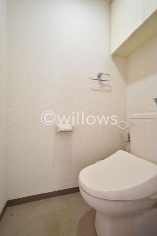 トイレは白を基調とし、清潔感のある空間に。お気に入りの絵画を飾ったり、小さなスペースでも工夫次第で素敵な空間になります。上部の吊戸棚はトイレ用品の収納が可能です。